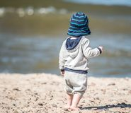 unge som går på sand på en strand fotografering för bildbyråer