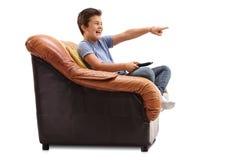 Unge som håller ögonen på något som är rolig på TV Royaltyfri Fotografi