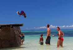 Unge som hoppar till havet royaltyfria bilder