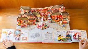 Unge som läser böcker som 3D introducerar kulturer om kinesiskt nytt år hemma royaltyfri fotografi