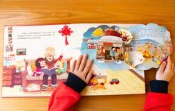 Unge som läser böcker som 3D introducerar kulturer om kinesiskt nytt år hemma arkivbilder