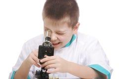 unge som ser mikroskopet Arkivbild