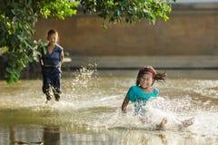 Unge som slippering på en översvämmad fyrkant Arkivfoto