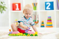 Unge som spelar med byggnadskvarter på dagiset Royaltyfri Foto