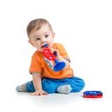 Unge som spelar med den isolerade musikaliska leksaken Royaltyfri Bild