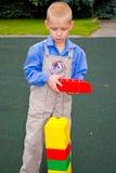 Unge som spelar med kuber Arkivfoto