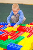 Unge som spelar med kuber Arkivbild