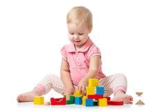Unge som spelar med träkvarterleksaker Behandla som ett barn flickabyggnadsslotten genom att använda kuber Bildande leksaker för  fotografering för bildbyråer