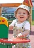 Unge som spelar på lekplats Royaltyfri Bild