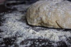 Ungebackener Teig auf dem Tisch mit dem Mehl herum lizenzfreies stockfoto