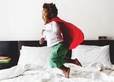 Ungebanhoppning för afrikansk nedstigning på sängen med ämbetsdräkten royaltyfri foto
