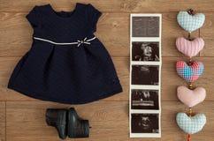 Ungeborener Baby Sonography und Mädchen-Kleid mit zusammenpassenden Schuhen in einer Ebene gelegt auf Holzoberfläche Stockbilder