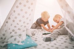 Ungebröder lägger på golvet Pojkar spelar i hem med leksakbilar hemma i morgonen tillfällig livsstil royaltyfri fotografi