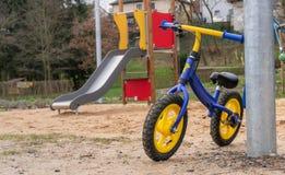 Ungecykel som parkeras på lekplats royaltyfria foton