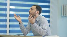 Ungeduldig männlicher Patient, der am Aufnahmeschreibtisch wartet Lizenzfreie Stockfotos