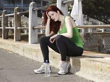 Ungeeigneter Läufer, der versucht, ihren Atem zu fangen Stockfotos