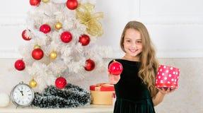 Ungeflicka nära asken för gåva för håll för julträd Barnet firar jul hemma Favorit- dag av året Tid som ska öppnas royaltyfria bilder