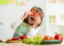 Ungeflicka som har gyckel med matgrönsaker arkivfoton