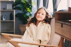 Ungeflicka som hemma kopplar av i hemtrevlig stol fotografering för bildbyråer