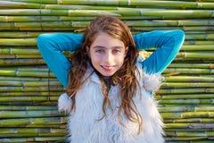 Ungeflicka som kopplas av i grön rottingbakgrund Fotografering för Bildbyråer