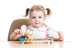 Ungeflicka som leker den musikaliska toyen arkivbild