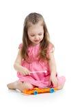 Ungeflicka som spelar den musikaliska leksaken Royaltyfria Bilder