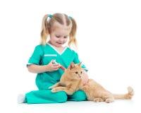 Ungeflicka som spelar doktorn med katten Royaltyfri Foto