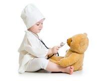 Ungeflicka som spelar doktorn med nallebjörnen Fotografering för Bildbyråer
