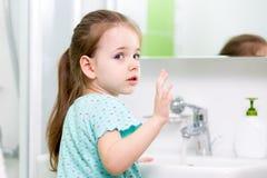 Ungeflicka som tvättar hennes framsida och händer i badrum Royaltyfri Foto