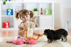 Ungeflickan matar hunden på golv i rum Royaltyfri Foto
