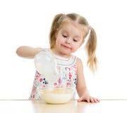 Barnflickan som förbereder havreflingor med, mjölkar Arkivbild