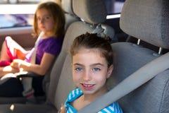 Ungeflickor med säkerhetsbältet i bil inomhus fotografering för bildbyråer