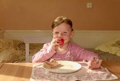 Ungegirll äter chokladpralinspridning på bröd Sött matmellanmål för choklad Den lyckliga flickan har ett mellanmål i köket A Arkivfoton