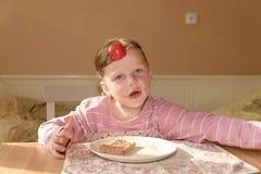 Ungegirll äter chokladpralinspridning på bröd Sött matmellanmål för choklad Den lyckliga flickan har ett mellanmål i köket A Royaltyfri Fotografi