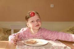 Ungegirll äter chokladpralinspridning på bröd Sött matmellanmål för choklad Den lyckliga flickan har ett mellanmål i köket A Royaltyfri Bild