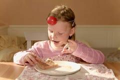 Ungegirll äter chokladpralinspridning på bröd Sött matmellanmål för choklad Den lyckliga flickan har ett mellanmål i köket A Arkivfoto