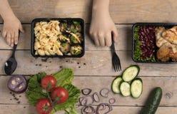 ungehänder med den svarta skeden och gaffeln under matbehållaren med grillade fega vingar, blå handduk royaltyfri foto