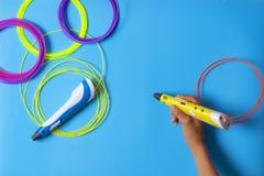 Ungehand som rymmer pennan 3d med den plast- glödtråden på blå bakgrund arkivfoton
