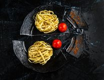 Ungekochte italienische Fettuccine-Teigwaren auf einem defekten Schwarzblech mit Cherry Tomatoes lizenzfreies stockbild