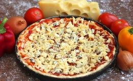 Ungekochte Pizza mit Bestandteilen auf hölzernem Hintergrund Stockfoto