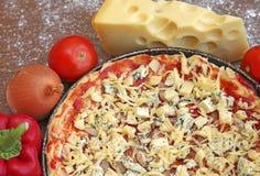 Ungekochte Pizza mit Bestandteilen auf hölzernem Hintergrund Lizenzfreies Stockbild