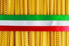 Ungekochte Spaghettiteigwaren Authenric Tripoline mit italienischen Flaggenartbändern Stockfotos
