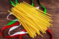 Ungekochte Spaghettiteigwaren Authenric Tripoline mit italienischen Flaggenartbändern Stockbild