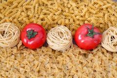 Ungekochte Teigwaren mit Tomate in der Mitte Lizenzfreie Stockfotos