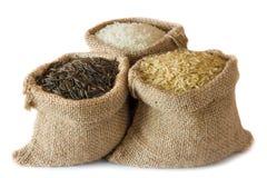 Ungekochter Reis in den kleinen Leinwandsäcken stockfotos