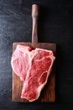 Ungekochtes Steak des förmigen Knochens auf einem hölzernen Brett Stockbilder