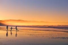 Ungekontur som spelar och har gyckel i strand på solnedgången Royaltyfria Bilder