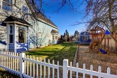 Ungelekplats i trädgården av det blåa hantverkarehemmet Royaltyfri Foto