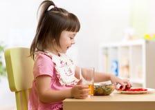 Ungeliten flicka som äter sunda grönsaker Arkivbilder