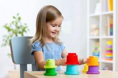 Ungeliten flicka som spelar med leksaker inomhus royaltyfria bilder